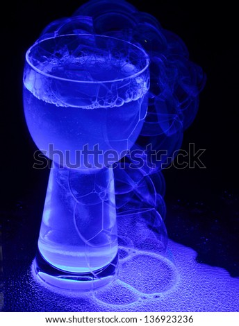 A sudsy drink caused to glow with an ultraviolet light