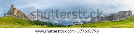 A summer alpine panorama of a wide italian valley under the Passo di Giau mountain pass with a dark dramatic cloudy storm sky, steep rocky walls, haze and fresh green pastures #577638796
