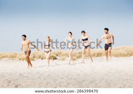 A summer day on a sandy beach, a group of five young people run towards the sea to swim. People are in swimwear on the beach and there are no other people.