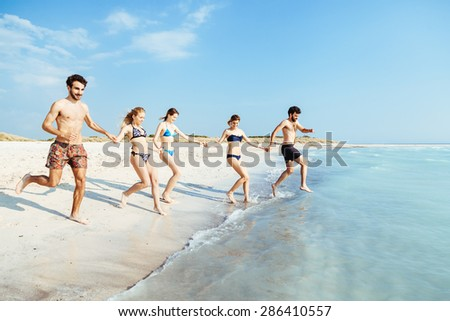 A summer day on a sandy beach, a group of five young people run towards the sea to swim. People are in swimwear on the beach and there are no other people