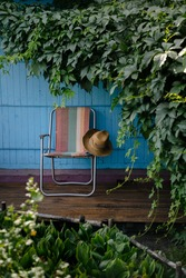 A summer hat and a folding chair surrounded by green vine leaves on a wooden deck. Relaxation in the garden. Cottage aesthetics. Vacation outside the city. Warm summer day.