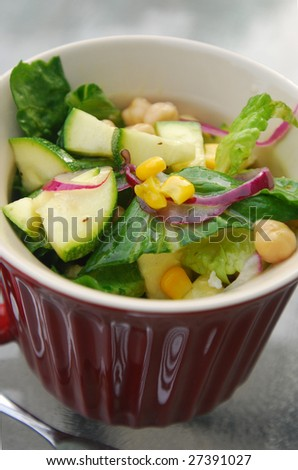A summer salad in a ceramic bowl that includes, lettuce, garbanzo beans (chick peas), corn, onions, and zucchini.