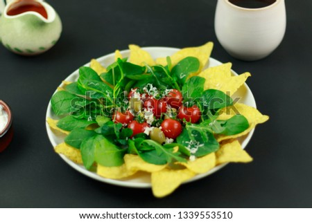 A sumptuous plate of cherry tomatoes, green olives and green salad leaves on a bed of corn chips. A mug of coffee and a jug of salsa complete the picture.