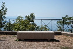 A sun-drenched bench sits on an elevated panoramic point on the via Napoleonica in Trieste, Italy