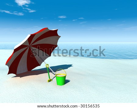 A sun parasol, bucket and spade on a beach by the sea on a sunny summer day.