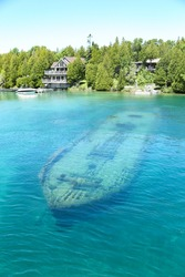A sunk old wood boat under lake in portrait view