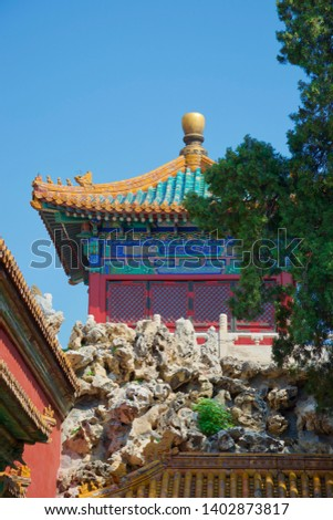 A sunlit rockery and tree in foreground, with a vibrant, brightly painted Chinese temple (pagoda) in gold, blue, green and red against bright sky #1402873817