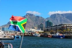 A sunny day by the Victoria and Albert Waterfront in Cape Town South Africa, with South African flag and Table Mountain in the distance