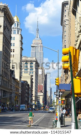 A sunny day in New York with a street and the Empire State Building in the background