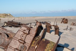 A sunny day with shipwrecks on a sandy beach in Norderney