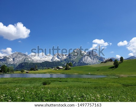 A sunny, peaceful mountain landscape with meadows, mountain lake, trees, huts, stables and snow-covered mountains, under a clear sky with cotton wool clouds. The high trail in the toggenburg valley #1497757163