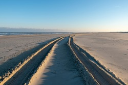 A sunny seashore with wheel track on sands in Norderney
