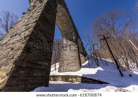 A sunny view of the underside of the historic stone arch New York, Susquehanna & Western Railway Starrucca Viaduct in Pennsylvania.