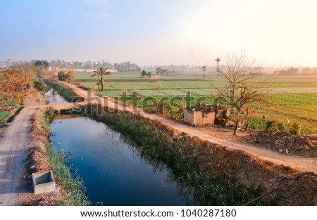 A sunrise view for a Canal ( Artifical waterway ) coming from the river nile passing through fields of farm lands in rural road Al Mehwar, Giza, Egypt.
