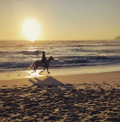 A sunset at the sea in Italy with a girl riding a horse running on the beach
