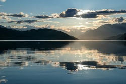 A sunset by Millstaetter lake in Austria. The lake is surrounded by high Alps. Calm surface of the lake reflecting the sunbeams. The sun sets behind the mountains. A bit of overcast. Natural beauty