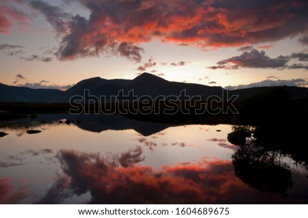 A sunset illuminates red clouds over the tranquil waters of Rannoch Moor, Highland, scotland