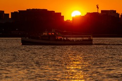 A sunset image featuring sun setting behind buildings, while a river cruise boat with passengers standing on deck is traveling in Potomac river that runs between Washington DC and virginia