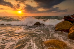 A Sunset Ocean Wave is Breaking on the Sea Shore with the Sun Setting on the Ocean Horizon