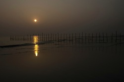A SUNSET ON SEA AND FANCING WITH BAMBOO AT GANGASAGAR , WESTBENGAL, INDIA