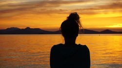 A sunset over a body of water and shadow of a women