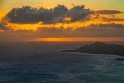 A sunset over the Hawaiian Island of Oahu as seen from a mountain top with Diamond Head in the distance.  Image captured from the summit of Koko Head Crater.