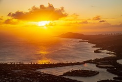 A sunset over the Hawaiian Island of Oahu as seen from a mountain top with the city of Hawaii Kia in the foreground and Diamond Head in the distance.  Image captured from the summit  Koko Head Crater