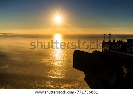A sunset over the Nazaré canion seen from visitors ata  viewpoint on a cold day showing mist and sunflare. Nazare is located at the centre of Portugal, famous for hosting surfing contests. #771736861