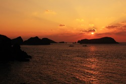 A sunset scene with the silhouette of islands and clouds on Jeju Island