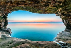 A sunset sky, reflected upon a calm Lake Superior, is framed by a sea cave along the Upper Peninsula coastline of Michigan.
