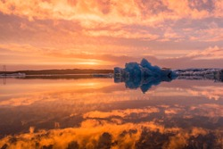 A sunset view of the glacier bay in Jökulsárlón with the main blue iceberg floating in the middle