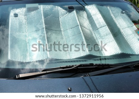A sunshade shields a car's interior against the heat as the intensity of the midday sun is reflected on the windscreen. #1372911956