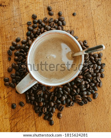 A super close up flat lay of a cup of coffee surrounded by coffee grains Photo stock ©