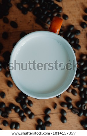 A super close up flat lay of a cup of milk surrounded by coffee grains Photo stock ©