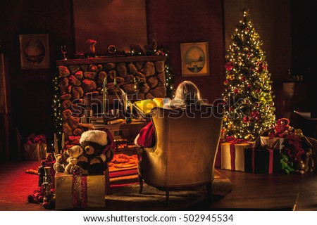 A super wide shot of Santa Claus in his workshop at the north pole, santa\'s office. We can see his is also using a cell phone / smart phone