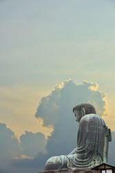 A superimposed or double exposures of The Great Buddha of Kamakura town, Japan, a bronze statue ofAmida Buddha with a beautiful dramatic and peaceful clouds and sky. Mindfulness and enlighten moment.