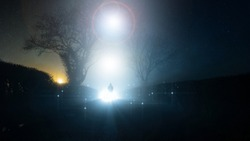 A supernatural, UFO concept of a scary, mysterious hooded figure, standing in front of a bright lights in the sky, on a country lane, on a spooky foggy winters night.