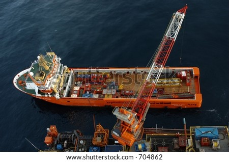 A supply ship being loaded and unloaded from on an offshore oil rig