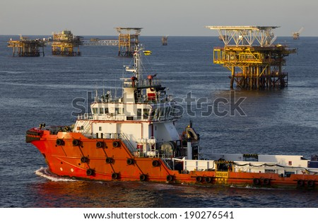 A supply vessel and rigs in an oil field