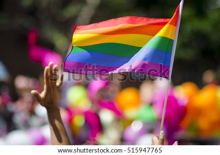 A supporting hand waves in front of a rainbow flag flying on the sidelines of a summer gay pride parade #515947765