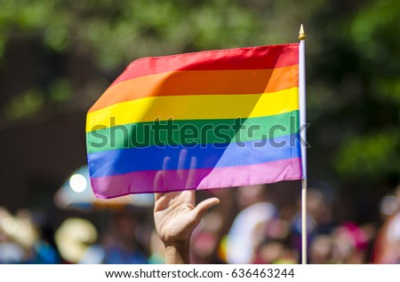 A supporting hand waving behind a rainbow flag flying on the sidelines of a summer gay pride parade #636463244
