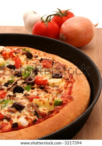 A supreme pizza in a pan with mixed vegetables