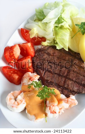 "A ""surf and turf"" meal of rump steak and prawns with salad and potatoes"