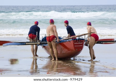 A surf boat team drag their boat across the sand to the water.