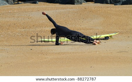 A surfer doing her yoga stretch before going in the sea