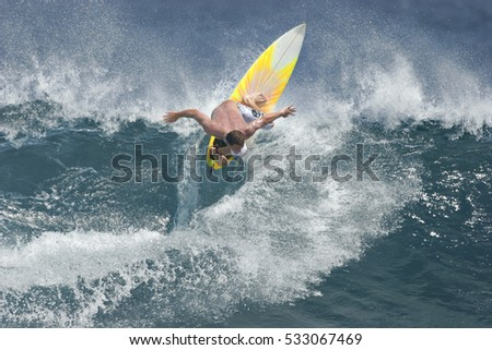A surfer executes a radical move on an ocean wave. #533067469