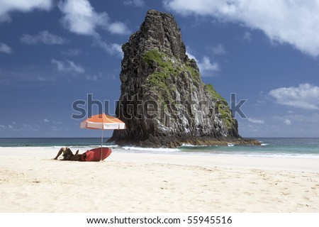 A surfer is laying under an umbrella waiting for waves. The deserted beach is shot against deep blue skies with few clouds and a huge rock in the middle. The picture is taken on Fernando de Noronha