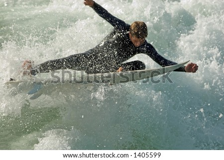 A surfer nearly does the splits as he slices through the beautiful California waves.