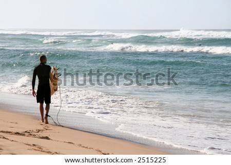 A surfer on the beach checking out the waves
