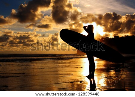 A surfer scopes out the waves during a sunset.